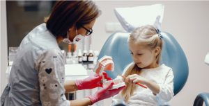 Little girl talking to the dendist. Child in the dentist's office. Woman in a uniform