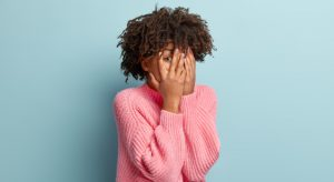 Photo Of Embarrassed Fearful Female Model Covers Face With Both Hands, Peeps Through Fingers, Observes Something Scarying, Hides Herself, Wears Loose Pink Jumper, Poses Indoor Over Blue Background